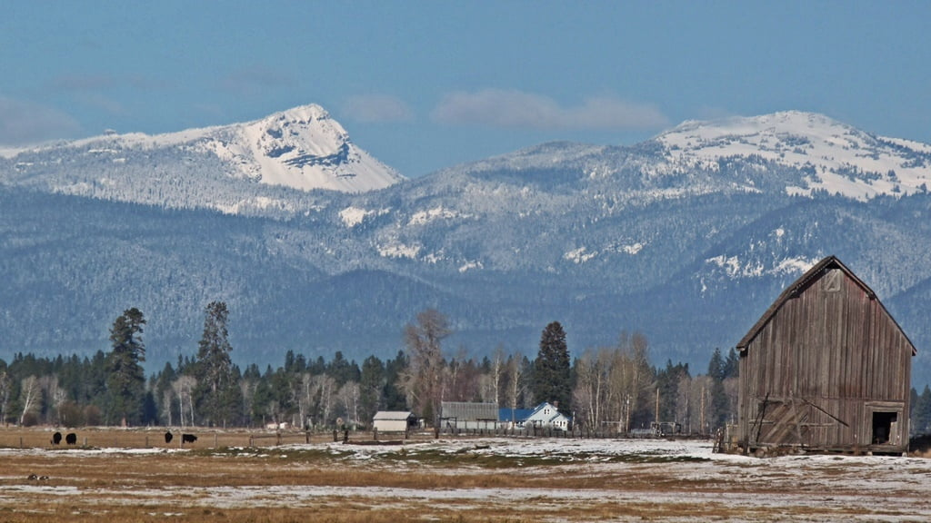 A tall barn and a tall peak on the Crater Lake rim, seen from Weed Rd in the Wood River Valley.