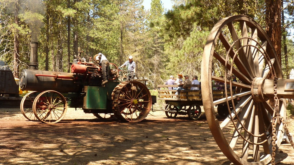 Hay rides on a wagon pulled by a steam tractor during Living History Day at Collier Memorial Sate Park and Logging Museum