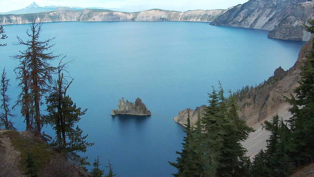 The 'Phantom Ship' rises 160 ft above the blue water of Crater Lake. Diamond Peak in the background.